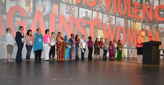 "Female delegates to the ITF Congress take the stage in support of the organization's ""white ribbon: campaign after workplace violence to women."